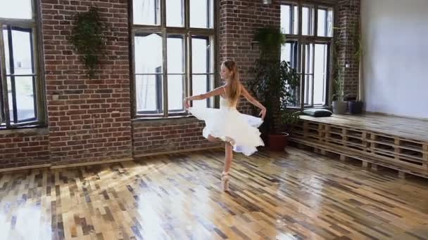Cute teenage ballerina in white ballet costume and pointe shoes is dancing in the dancehall in the ballet school. Graceful girl practicing elements ballet dance