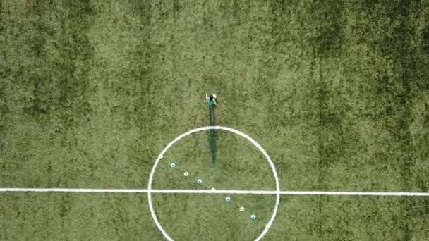 Mladí fotbalový hráč nakulato s fotbalovým míčem do brány.