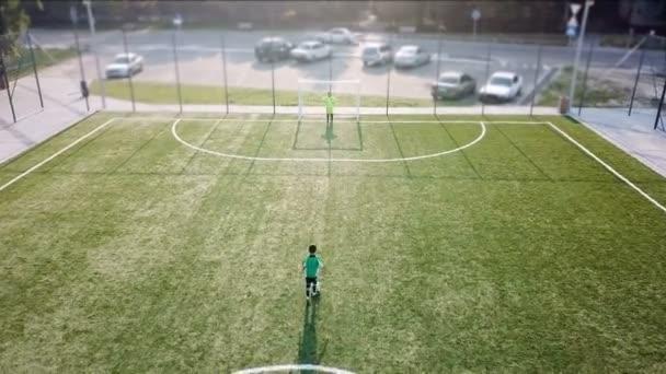 Malý fotbalista kope fotbalový míč do brány.