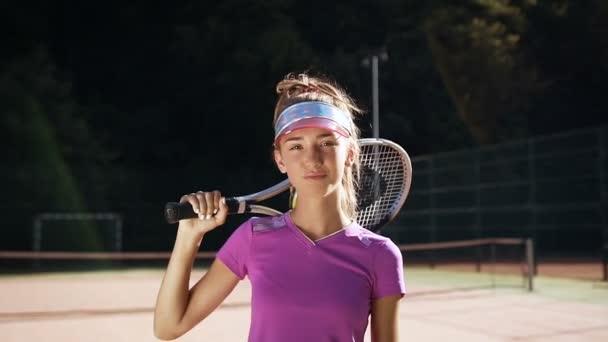 Mladá dívka s tenisovou raketu při pohledu na fotoaparát.