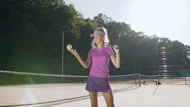 Mladá dívka v uniformě tenis tenisový míček na zvracení.
