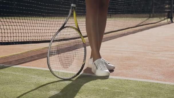 Ženské tenisové hráče spining raketu na zem a házecí tenisák.