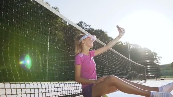 Atraktivní mladá žena sedící na tenisový kurt u net při pořizování selfie na chytrý telefon.