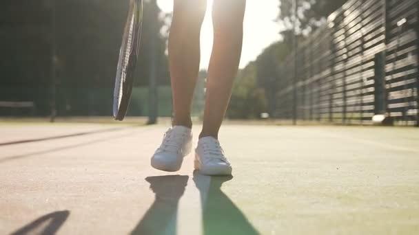 Detailní záběr záběr ženské tenisové hráče nohy s tenisovou raketu chůzi na kurtu