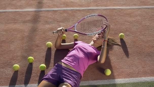 Mladá žena leží na tenisový kurt s mnoha míčky a hrát si s tenisovou raketu.