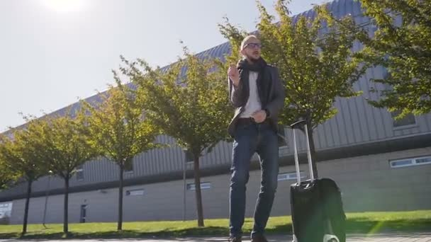 Happy bearded businessman in eyeglasses dressed in jacket with suitcase is dancing, celebrating achievement. Outdoors. Concept of office worker, rest, advertising, business, business trip