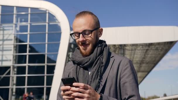 Close-up of a young businessman in glasses who is walking on urban streets, using modern smart phone - all this during a working lunch break at work. Professional male employer