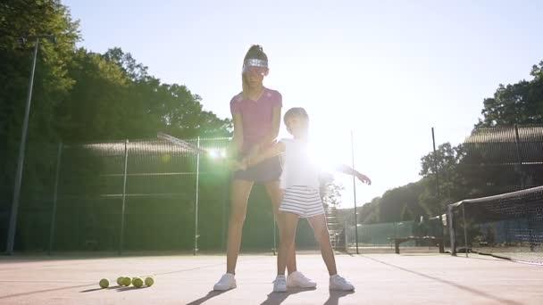 Atraktivní žena trenér učí holčička hraje tenis