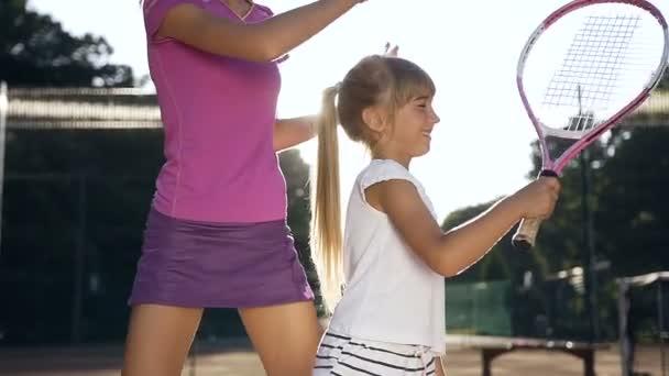 Mladé samice trenér s malou holkou během tenisový trénink
