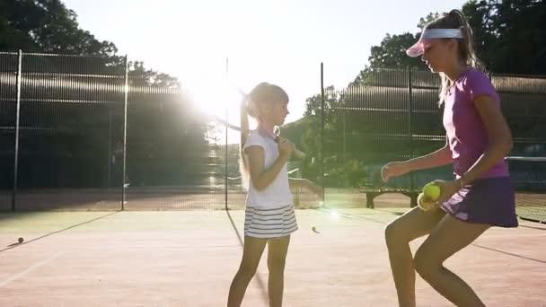 Pěkný ženský trenér dávat pět do malé tenista po tenisový trénink na hřišti