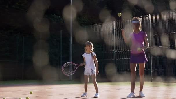 Pěkný ženský trenér házet míč a holčička udeří míč a chybějící