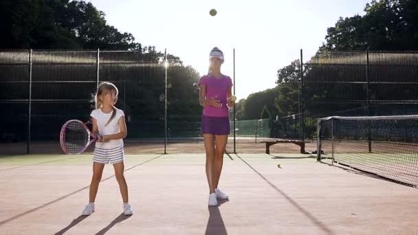Concantrate holčička udeří míč během tréninku s trenérem na kurtu.