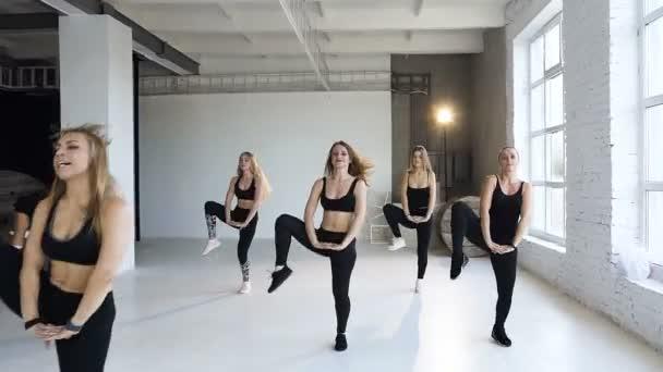 Csoport fiatal női aerobic fitness központ végezze el. Szép fitness lányok együtt gyakorolja a gyakorlás, fitness, aerobic, jóga, body egyensúlyt. Beltéri