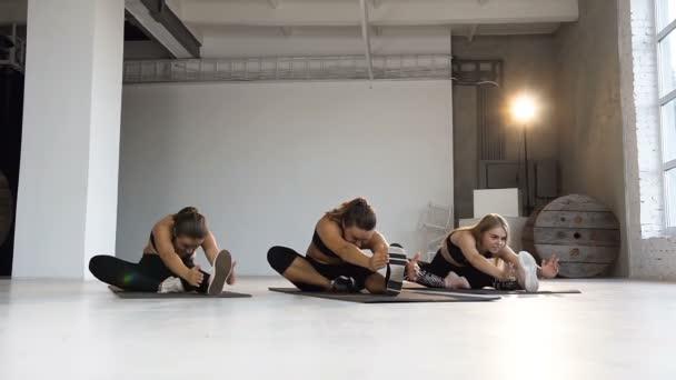 Mladé ženy v třídě jógy, meditace, dělá protahovací cvičení na podlaze. Sport, fitness, jóga, aerobik a zdravého životního stylu