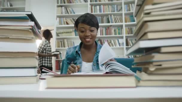 Mosolyogva afrikai női hallgató tanul, olvasás könyv a modern könyvtár.