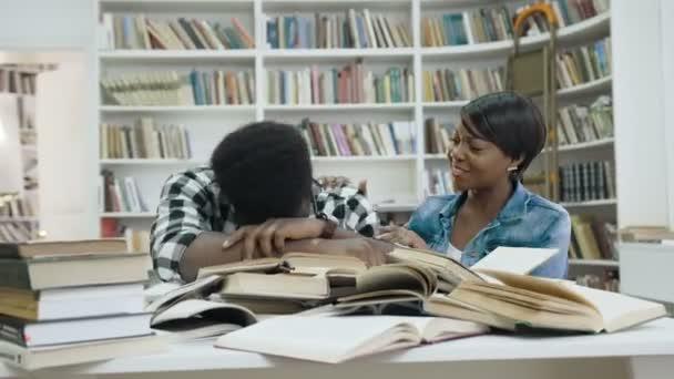 Unavený africké mladý muž spí na knihy, zatímco mladá Afričanka probudit ho v knihovně moderní.