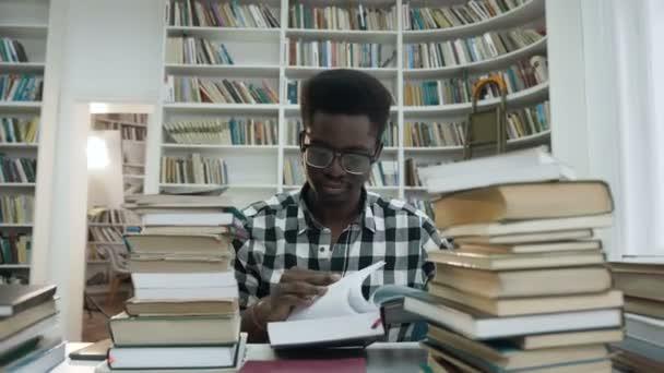 Szemüveg könyvével a könyvtárban ülve afrikai fiatalember portréja.