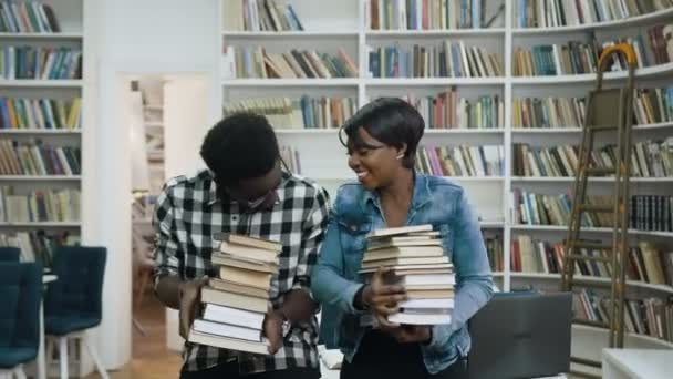 Young african couple holding a bunch of books in the hands while chatting and laughing on the library background.