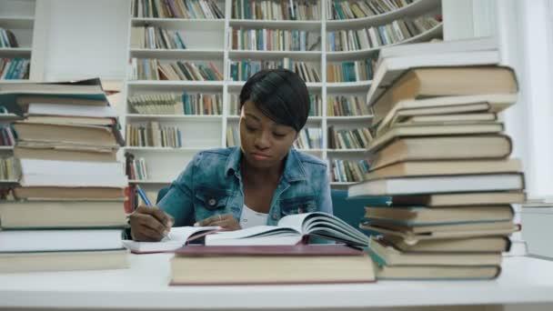 Africké studentka studuje, nějaké poznámky z knihy obklopen knihy v knihovně moderní.