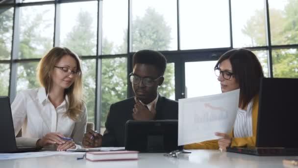 Kreative Business-Team-Meeting in modernen Glas Büro, Multi ethnischen Gruppe von Menschen mit neuen Projekt über Computer mit Berechnungen auf dem Papier kombiniert Teamarbeit Projekt