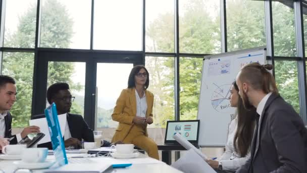 Young business woman gives presentation to multi-ethnic business group, coaching employees, explaining project charts on whiteboard and laptop, speaking about new marketing plan and new arrivals of