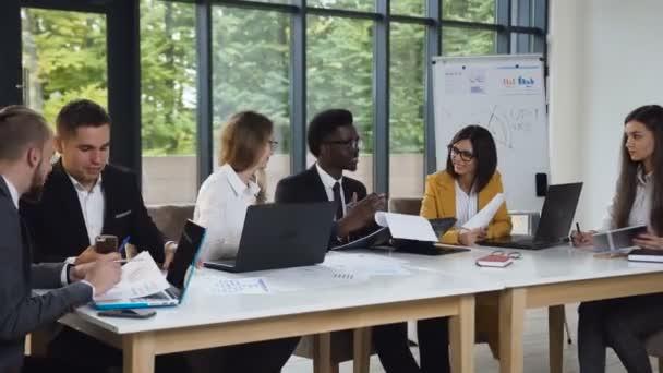 multiethnische Gruppe von Geschäftsleuten, die am Tisch sitzen und Ideen austauschen, während Geschäftstreffen in modernen Büros stattfinden. Kreative Geschäftsleute arbeiten gemeinsam an Projekt