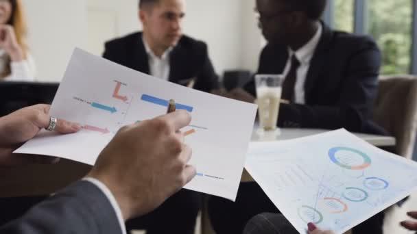 Közelkép kezében felismerhetetlen vállalkozókat keres dokumentumokat, grafikonok és diagramok használata-ülésen-a modern iroda munkatársai. Az üzleti koncepció