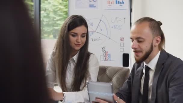 Dva podnikatelé lidí, kteří sedí v kanceláři tabulky a diskutovat o nové obchodní projekt, prohlížet dokumenty a grafiku na počítači tablet. Obchodní setkání mladých podnikatelů na úřadu