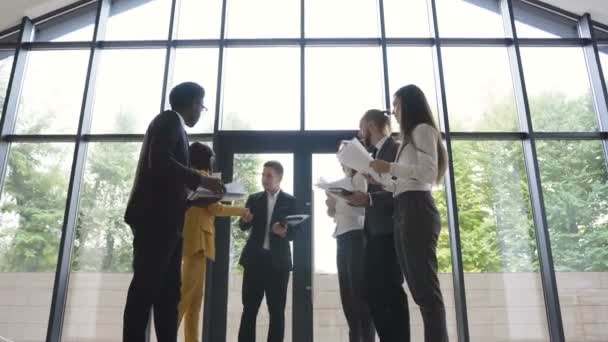 Confident and attractive young multi ethnic business team meet up with their colleagues shake hands and exchange documents, in a light and modern office
