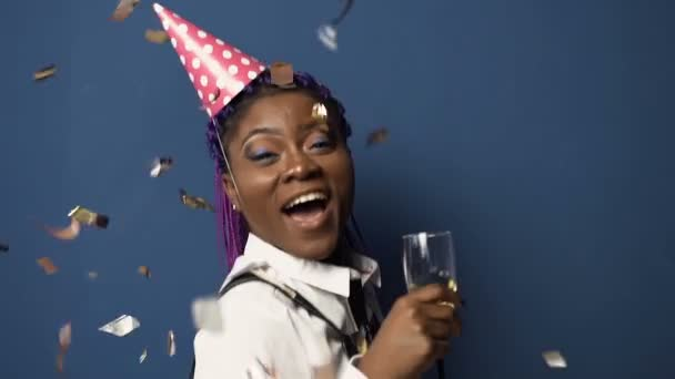 Attractive african girl in hat with champanage glass in hand, having fun and dancing while confetti flying down on the blue background.