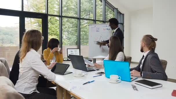 African american man drawing diagram on flipchart and holding to presentation for business colleagues at the corporate training in office with panoramic windows to the park