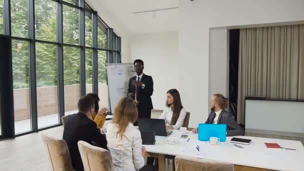 African american man making diagram on whiteboard and meeting brainstorming for business colleagues at the corporate training in office