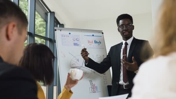 Young afro-american manager of company presenting new plan for project for team explaining business strategy using flipchart in office. Handsome speaker with flip chart reporting during the conference