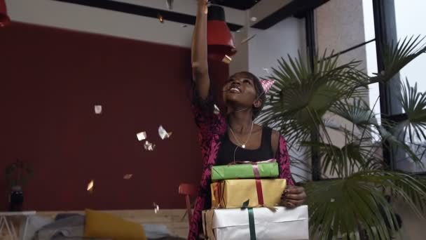 Portrait shot of happy african woman with boxes with gifts throwing gold confetti on the red room background.