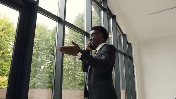 gutaussehender afroamerikanischer Geschäftsmann, der in der Lobby des Bürozentrums in der Nähe von Panoramafenstern steht und mit dem Smartphone spricht. Jungunternehmer kommuniziert selbstbewusst auf Smartphone