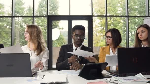A dokumentumok és a technológia a modern irodai asztal mögött ülve dolgozó fiatal multyethnic csoportja. Papírok nagy cégnél dolgozó üzletemberek