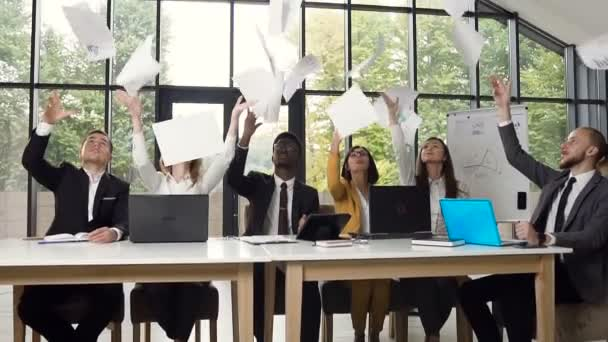 Young multiethnic business people throwing papers in air during meeting, celebrating new contract and new achievement. Successful business team at the office