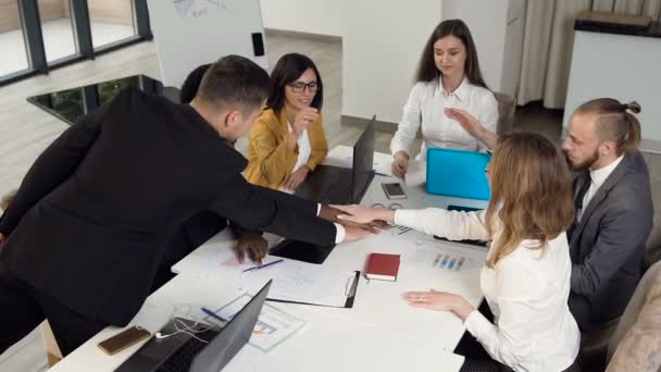 Successful business team working showing unity with their partners giving five to each other, sitting at conference table in office. Full concentration at work