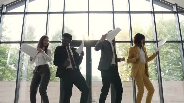 Diverse group female and male business team are celebrating success of company and throwing papers documents, Happy business people have fun dancing in modern at office near panoramic windows