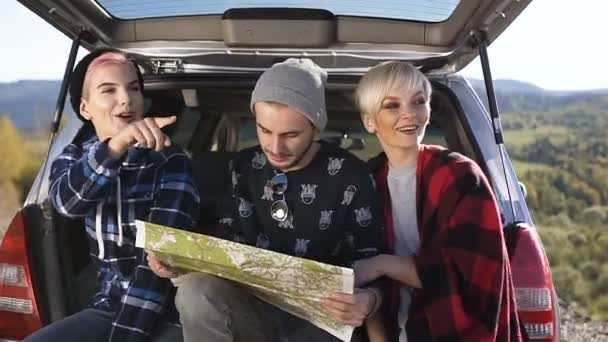 Dvě mladé ženy a jeden muž pomocí mapování pro hledání správné cestě při posezení v kufru auta.