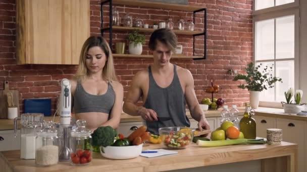 Mladý pár ve sportovním oblečení, stojící za kuchyňským stolem, připravuje čerstvý salát se zeleninou v kuchyni doma. Pohledný mladý muž se vyžívá v žluté paprice a pokouší se nakrájet