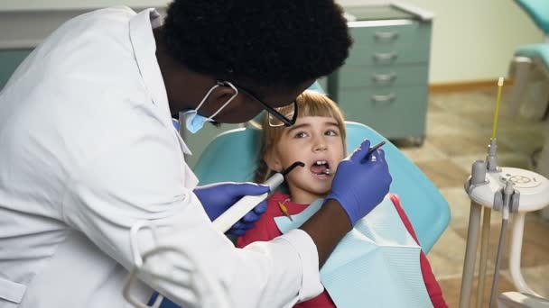 Dolly shot of african male dentist treating teeth of little girl.