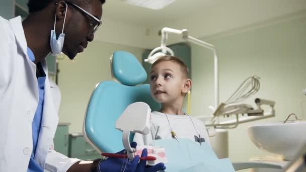 Africký muž zubař zobrazeno plastikový model zubů do malého muže.