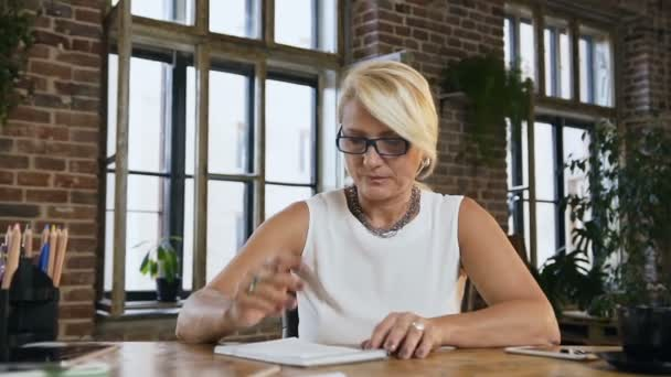 Atraktivní zaneprázdněná žena v brýlích něco záznamy v deníku sedí za stolem v kanceláři. Uvnitř. Koncept podnikání, vzdělávání a lidé