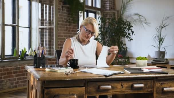 Attractive female teacher is checking something in the diary while drinks coffee sitting behind the desk in home office .Indoors. Business, education and people concept