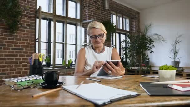 Adult Caucasian businesswoman is working using digital tablet computer, brainstorming creative ideas planning new idei in office at home