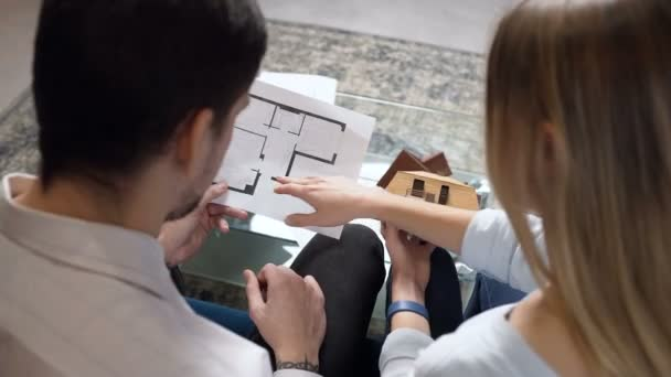 Young couple discussing blueprint and house model of future home.