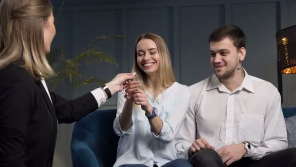 Happy attractive couple getting key from the real estate agent.