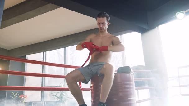 Mladý muž boxer obtékání červené obvazy v tělocvičně.