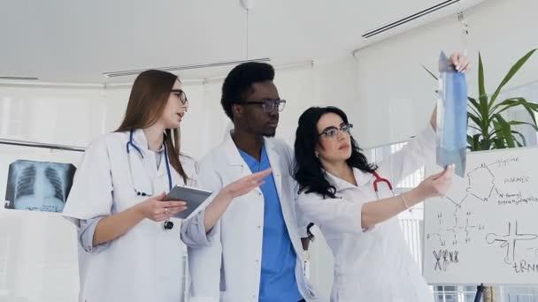Třemi multi národní lékaři diskutovat xray plic pacienta během pracovního dne